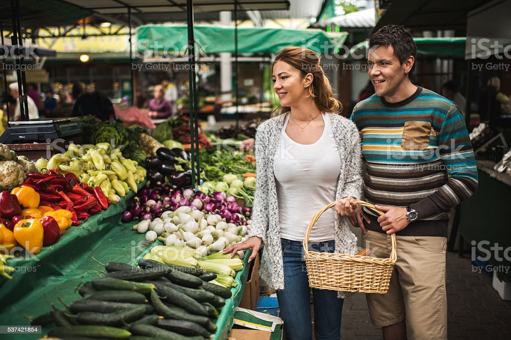 Young smiling couple buying groceries together on farmer's market. stock photo