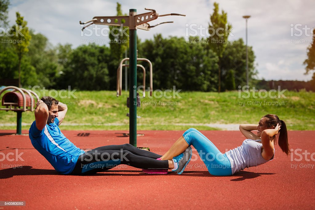 Young smiling couple doing sit-ups at outdoor gym. stock photo