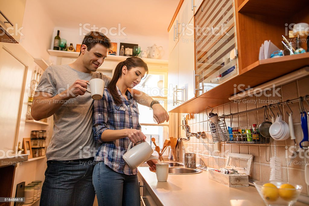 Young smiling couple in the kitchen. stock photo