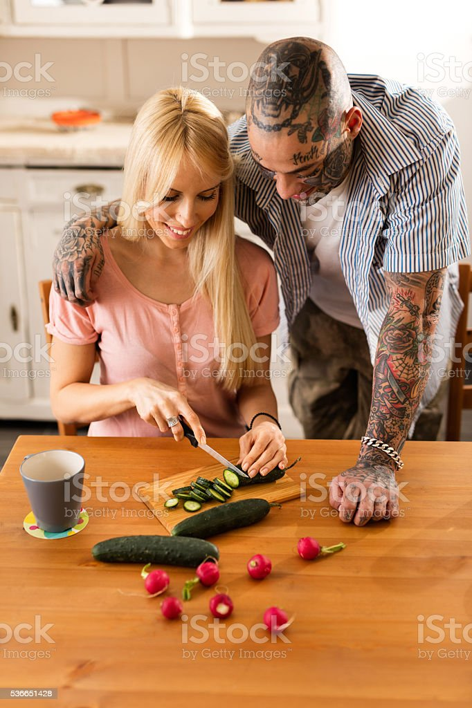 Young smiling couple preparing healthy food in the kitchen. stock photo