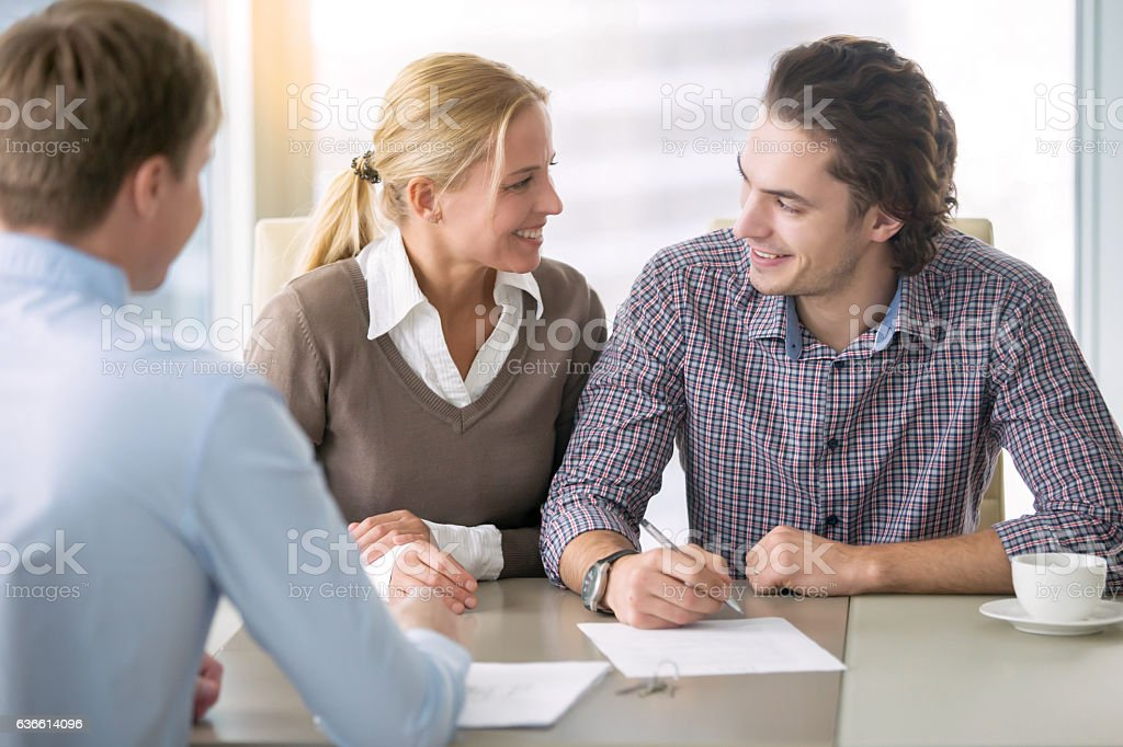 Young smiling couple signing a loan stock photo