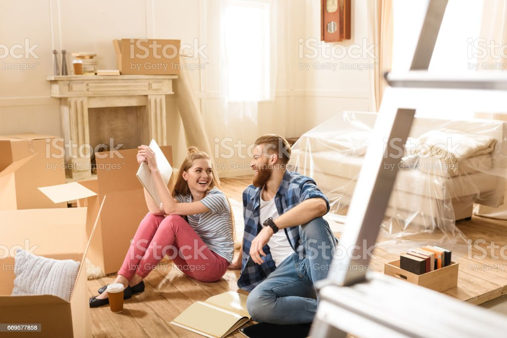 Young smiling couple sitting on floor near cardboard boxes stock photo