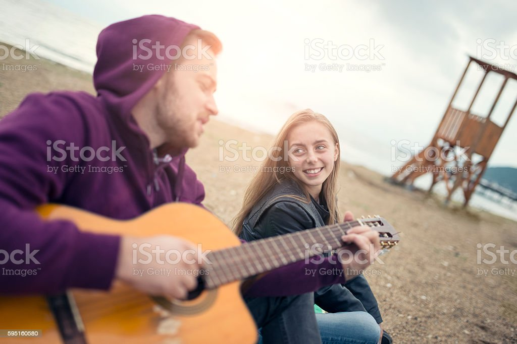 Young Smiling Couple with Acoustic Guitar Singing at Beach Party stock photo