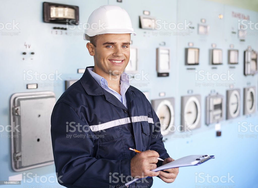 Young smiling engineer taking notes stock photo
