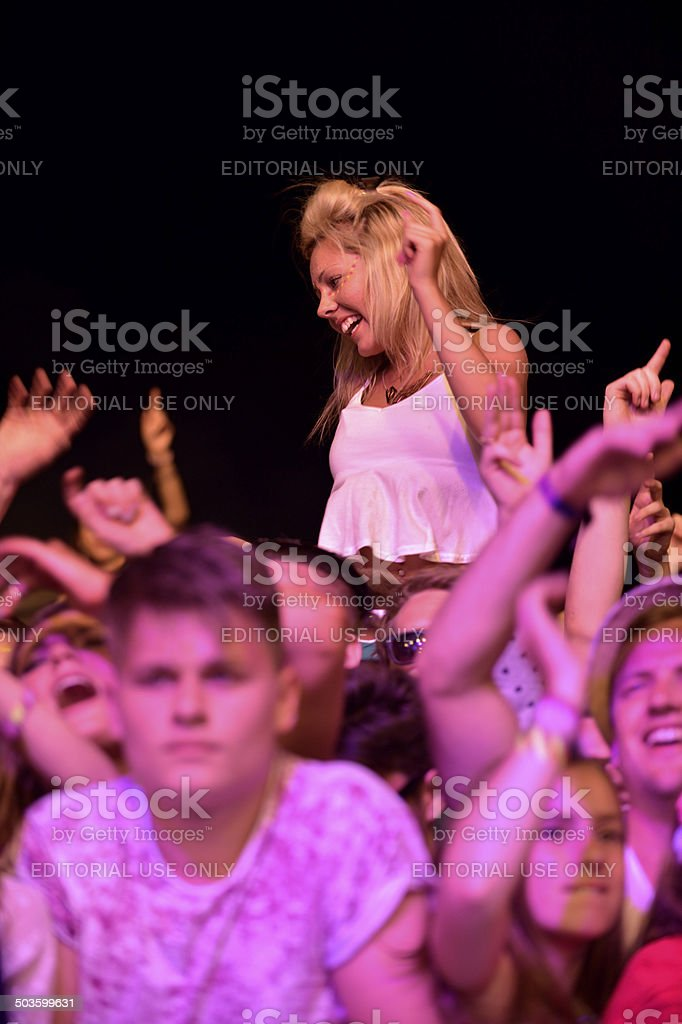 Young smiling female above the crowd at a music festival stock photo