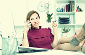 young smiling female employee sitting relaxed with legs on worki