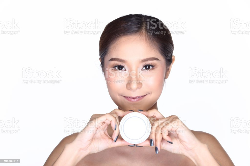 Young smiling female holding a white blank round jar bottle of Cosmetic skin care package product stock photo