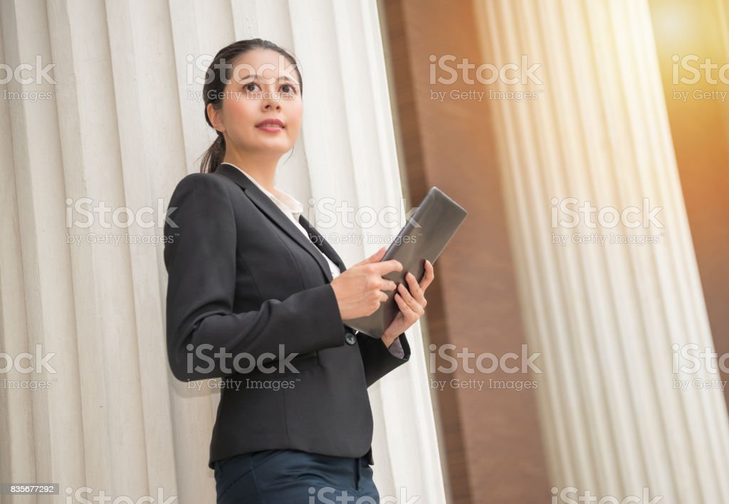 young smiling female lawyer holding mobile pad stock photo