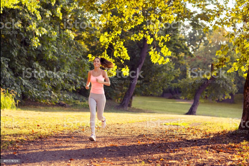 Young smiling fitness woman running in summer nature stock photo