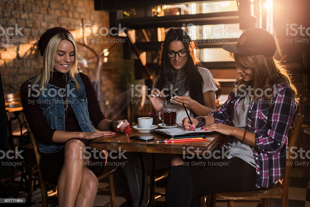 Young smiling friends doing different things in a cafe. stock photo