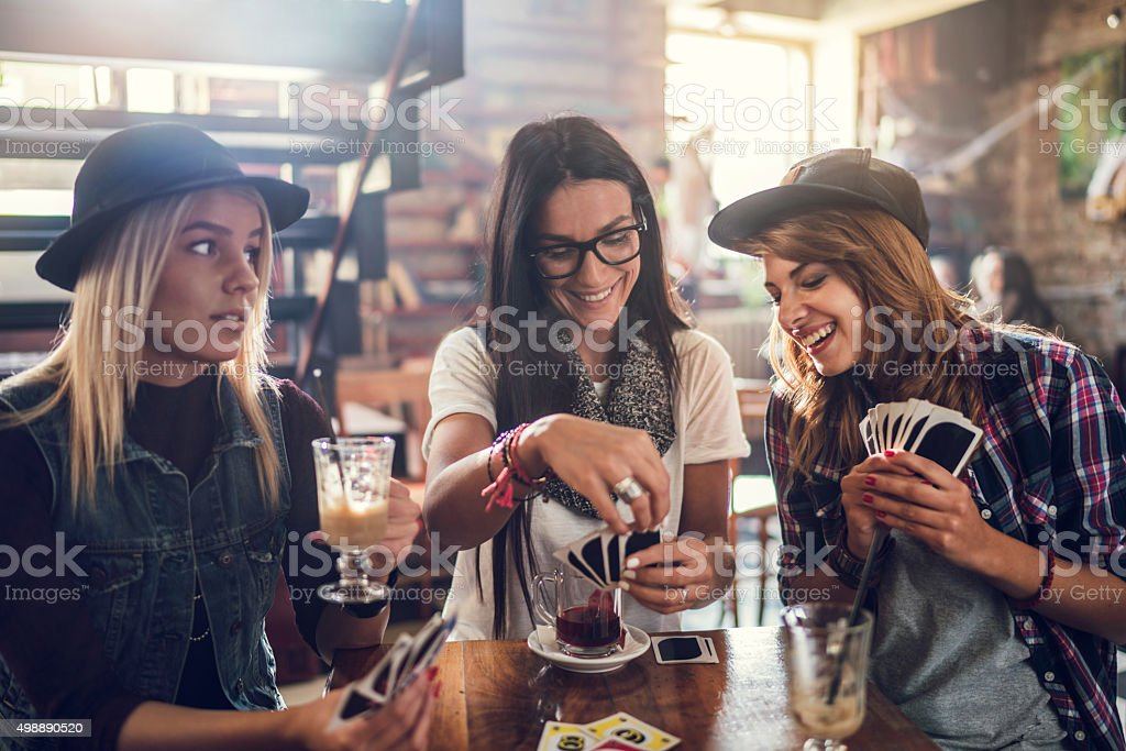 Young smiling friends playing cards in a cafe. stock photo