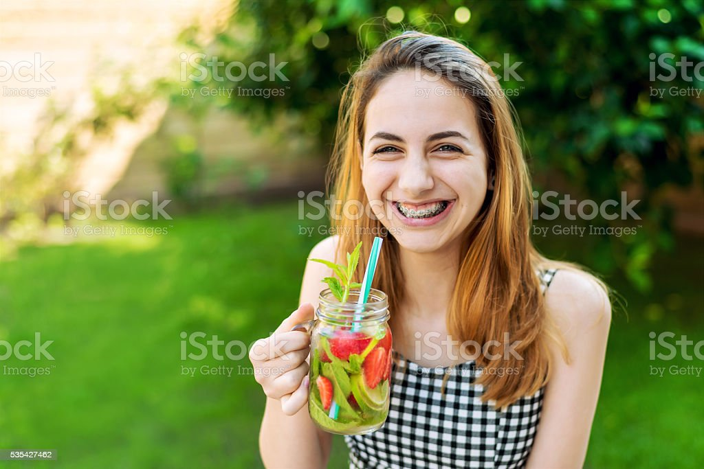Young smiling girl drinking tasty cocktail , outdoor terrace. stock photo