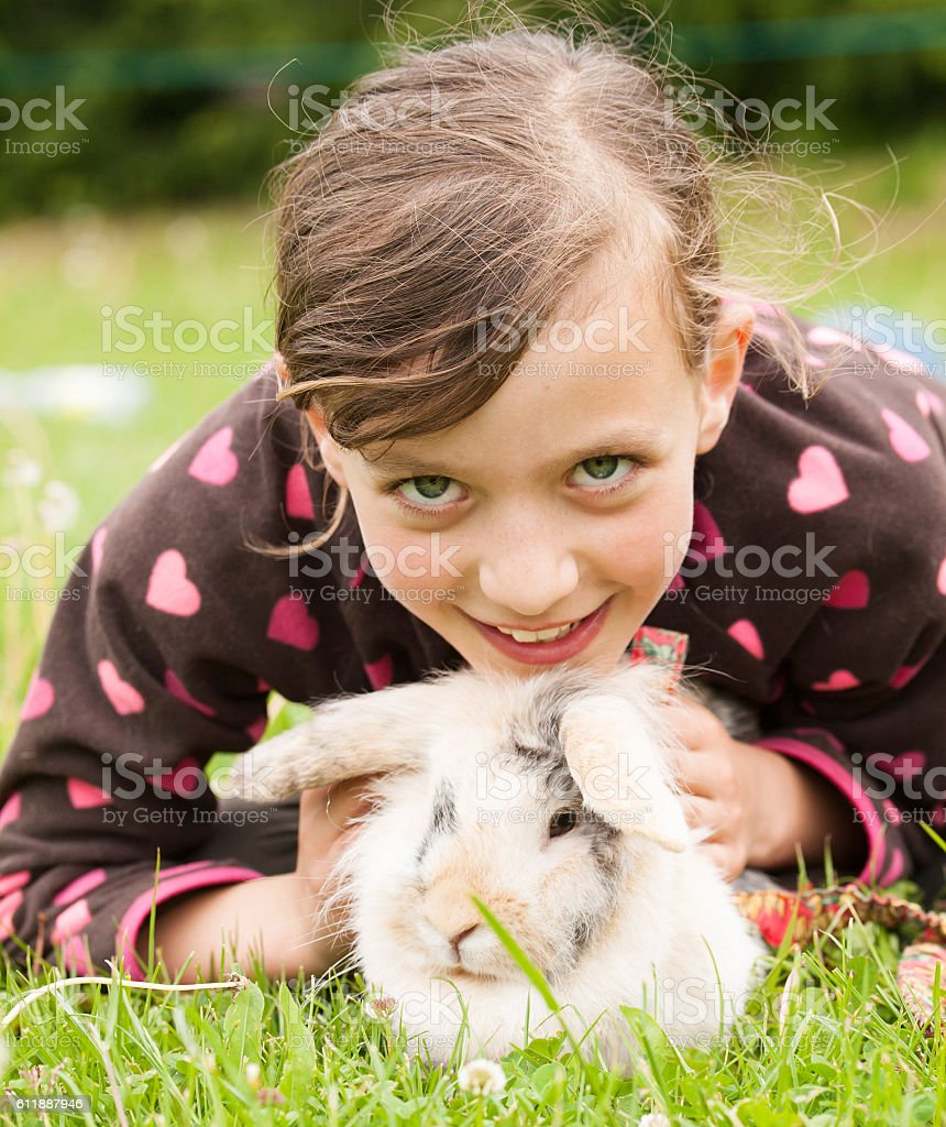 Young smiling girl with her rabbit pet stock photo