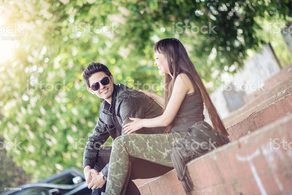 Young Smiling Hipster Couple Having Fun in the City Park stock photo
