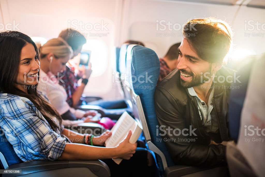 Young smiling man flirting with beautiful woman in airplane. stock photo