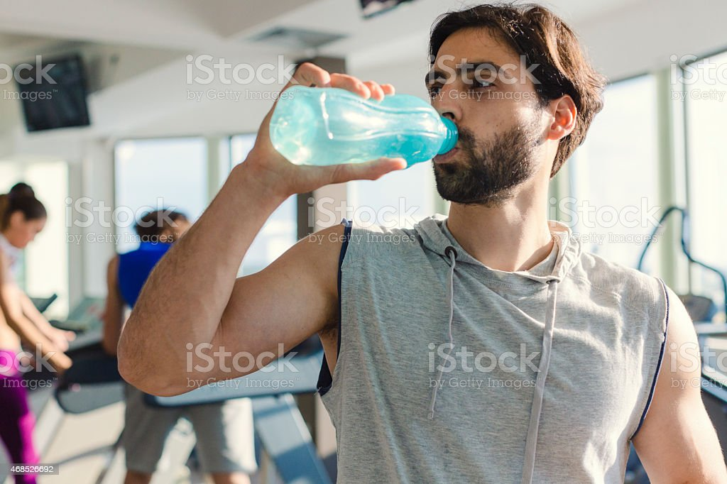 Young smiling man in a gym drinking water stock photo 468526692 young smiling man in a gym drinking water royalty free stock photo sciox Gallery