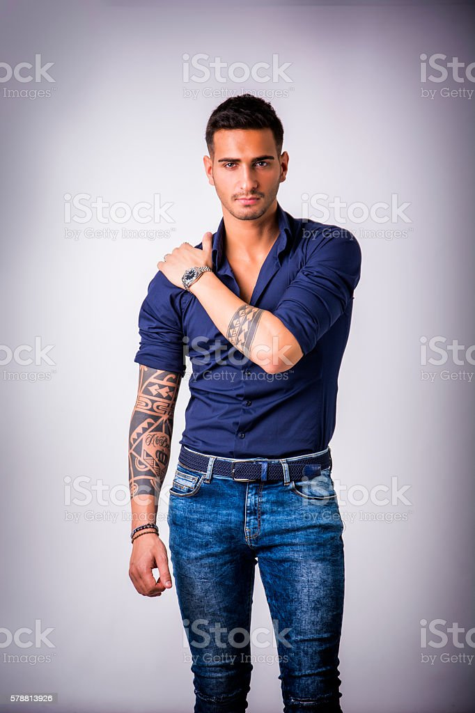 Young smiling man in blue shirt and jeans stock photo