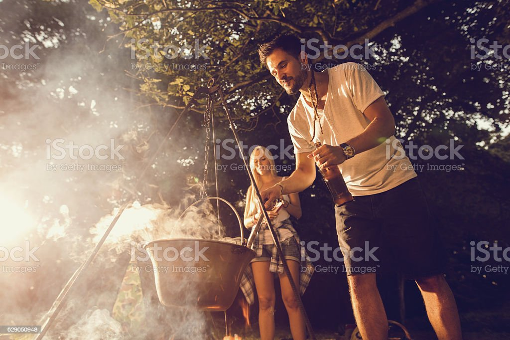Young smiling man preparing food in the forest. stock photo