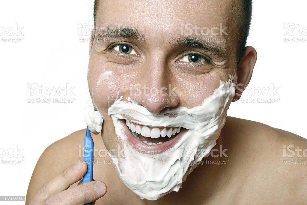 Young smiling man shaving with razor.Isolated on white. royalty-free stock photo