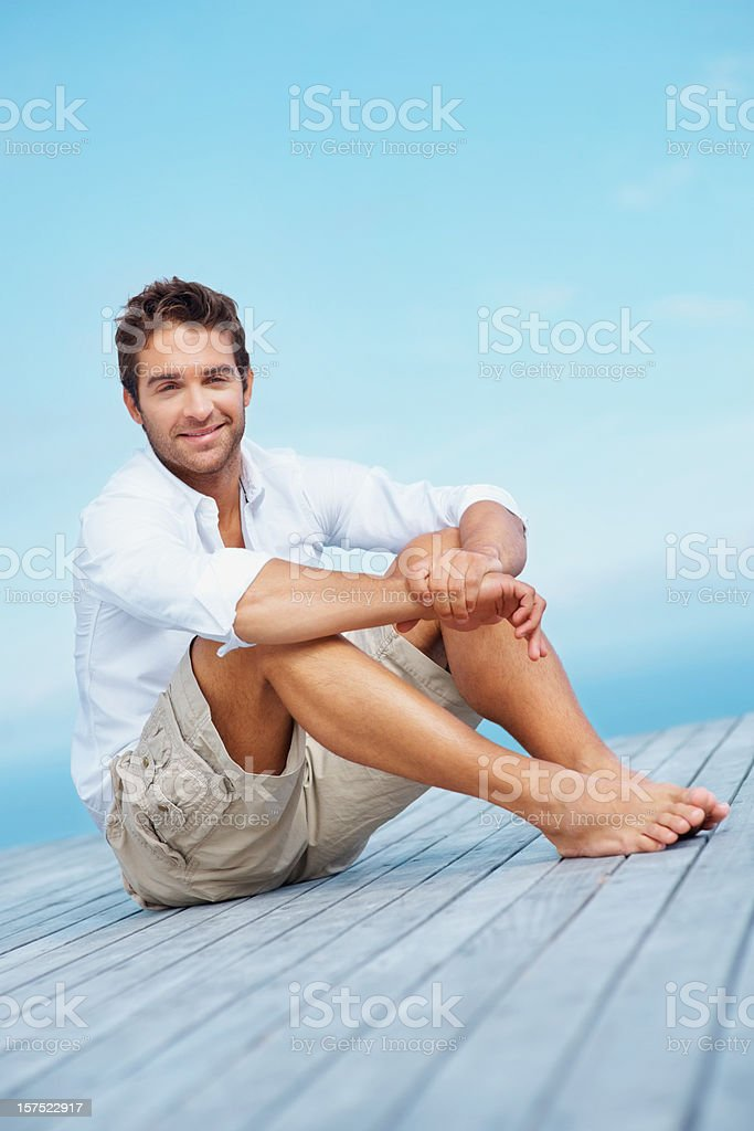 Young smiling man sitting alone on a porch royalty-free stock photo