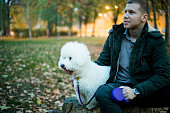 Young smiling man with pet in autumn park