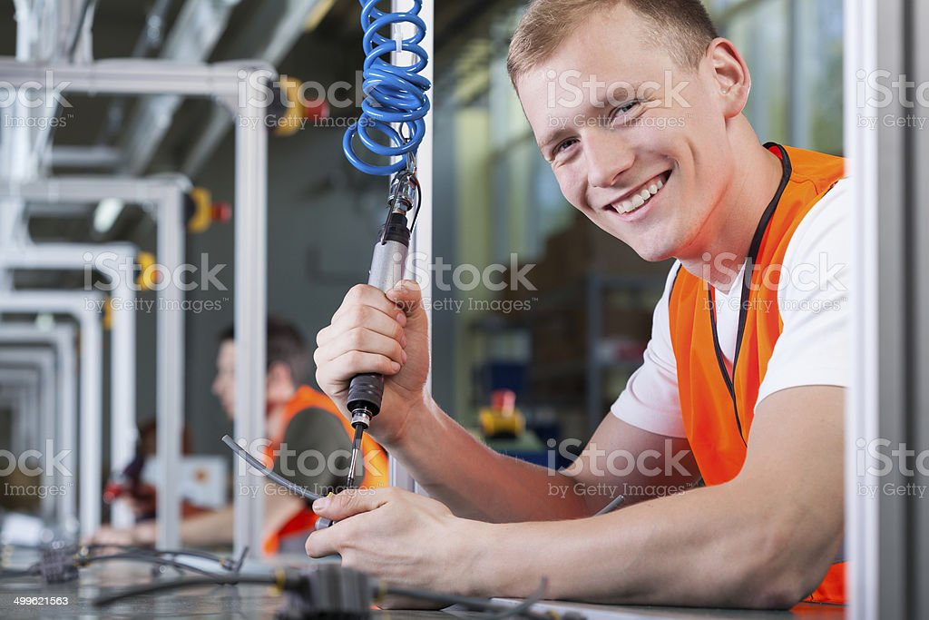 Young smiling man working on the production line stock photo