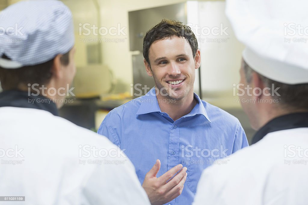 Young smiling manager talking to the staff stock photo