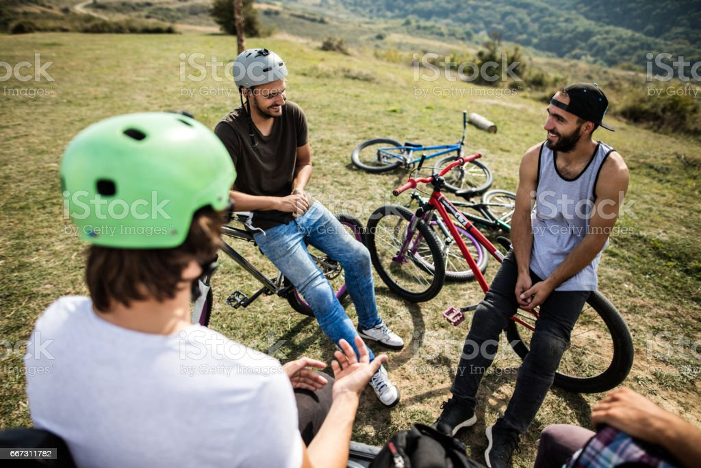 Young smiling mountain bike riders relaxing in nature. stock photo