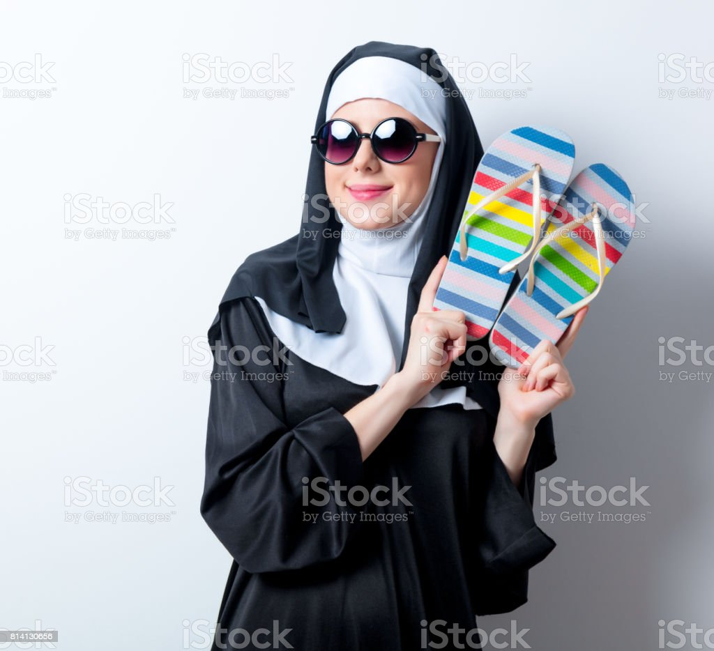Young smiling nun in sunglasses with flip flops stock photo