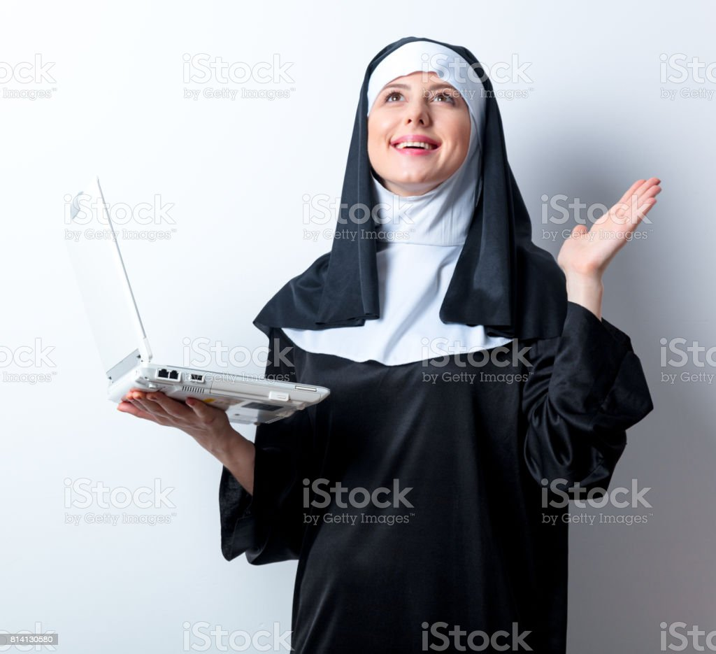 Young smiling nun with laptop computer stock photo