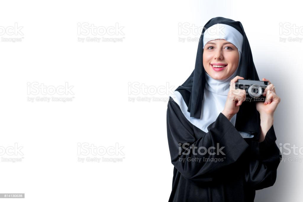 Young smiling nun with photo camera stock photo