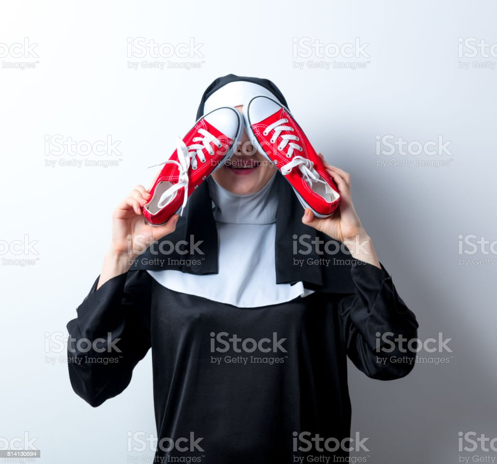 Young smiling nun with red gumshoes stock photo