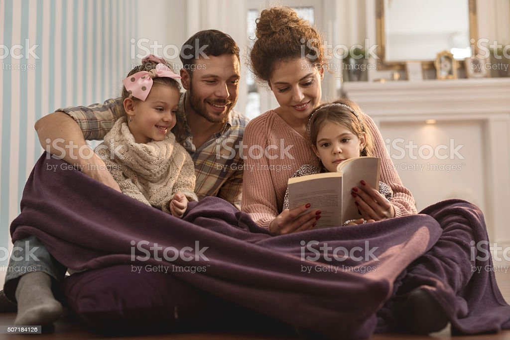 Young smiling parents reading a book to their small daughters. stock photo