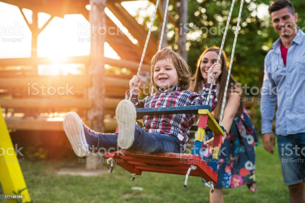 Young smiling parents swinging their son at sunset. stock photo