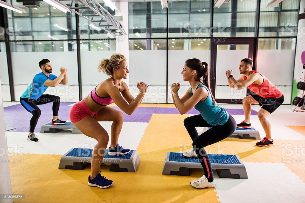 Young smiling people having step aerobics training in a gym. stock photo