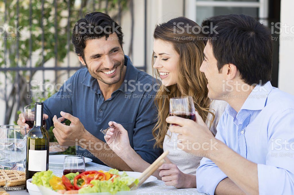 Young smiling people sitting at table outdoors stock photo