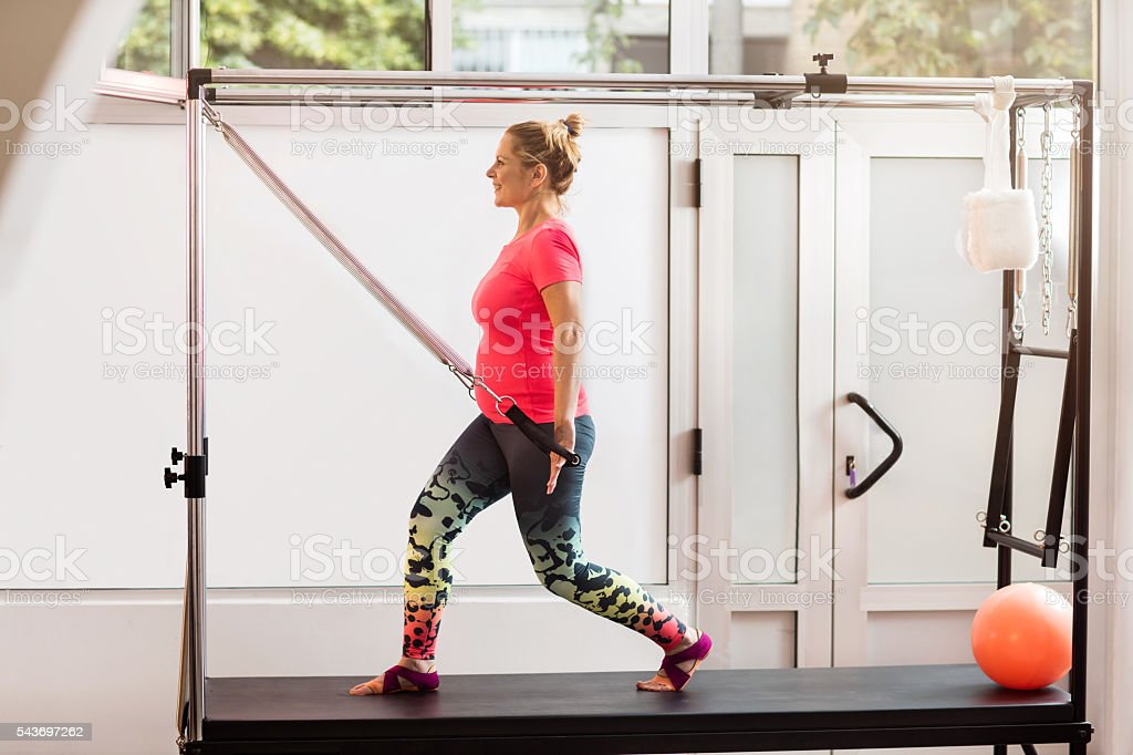 Young smiling pregnant woman working out on Pilates machine. stock photo