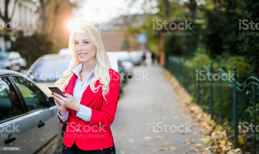 Young smiling secretary woman using a smartphone on a street stock photo