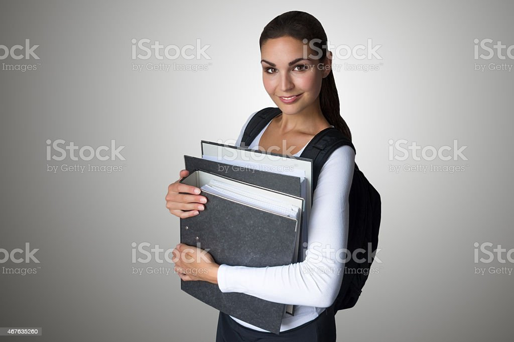 Young, smiling student holding folders stock photo