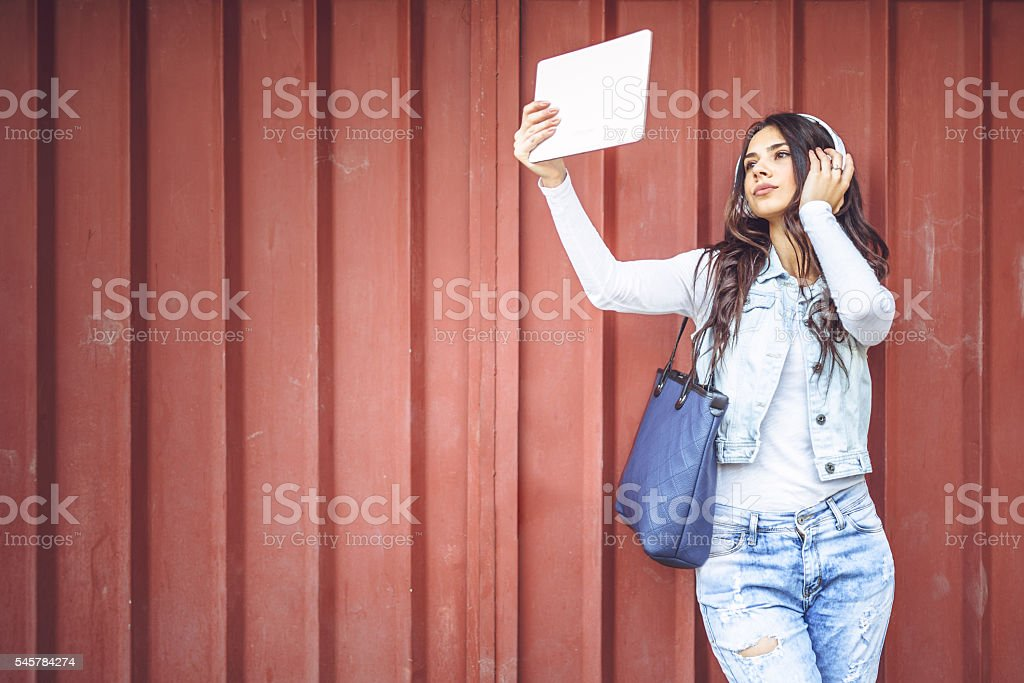 Young smiling student with headphones takeing a selfie stock photo