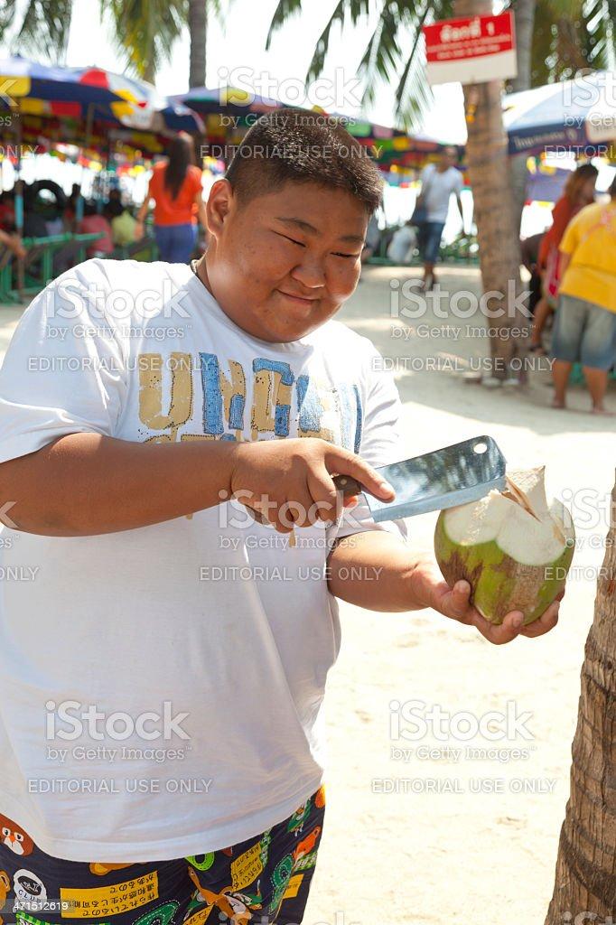 Young, smiling Thai man opening coconut on Bangsaen Beach royalty-free stock photo