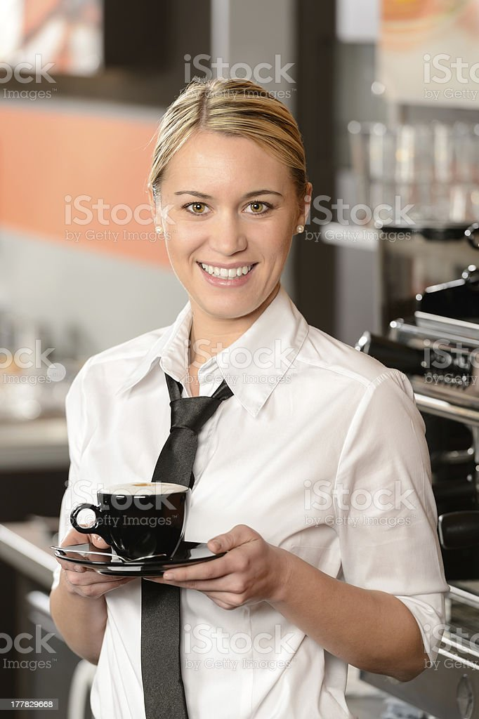 Young smiling waitress with cup of coffee royalty-free stock photo