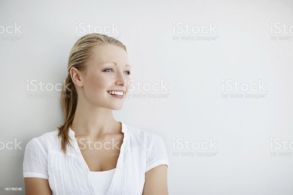 Young smiling woman against a wall looking at copyspace royalty-free stock photo