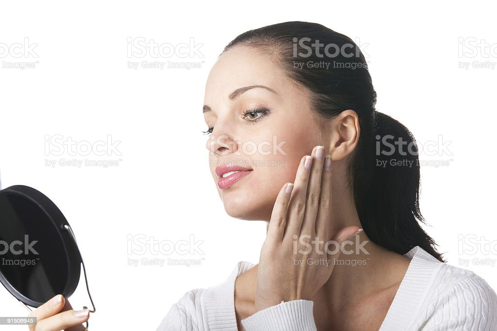 Young smiling woman applying cosmetics with mirror, isolated royalty-free stock photo