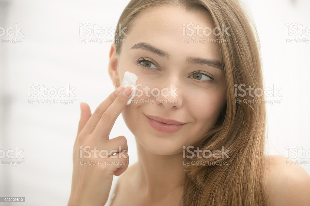 Young smiling woman applying cream to face in the bathroom stock photo