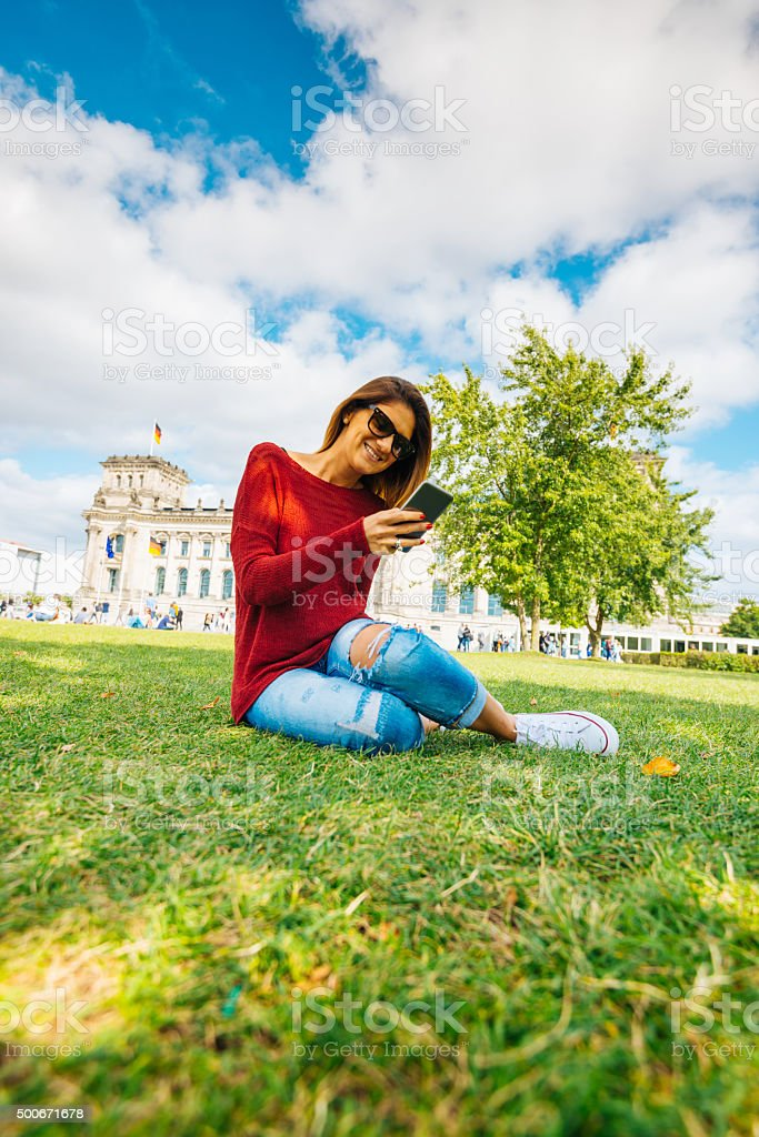 Young smiling woman browsing social media on smart-phone in Berlin stock photo