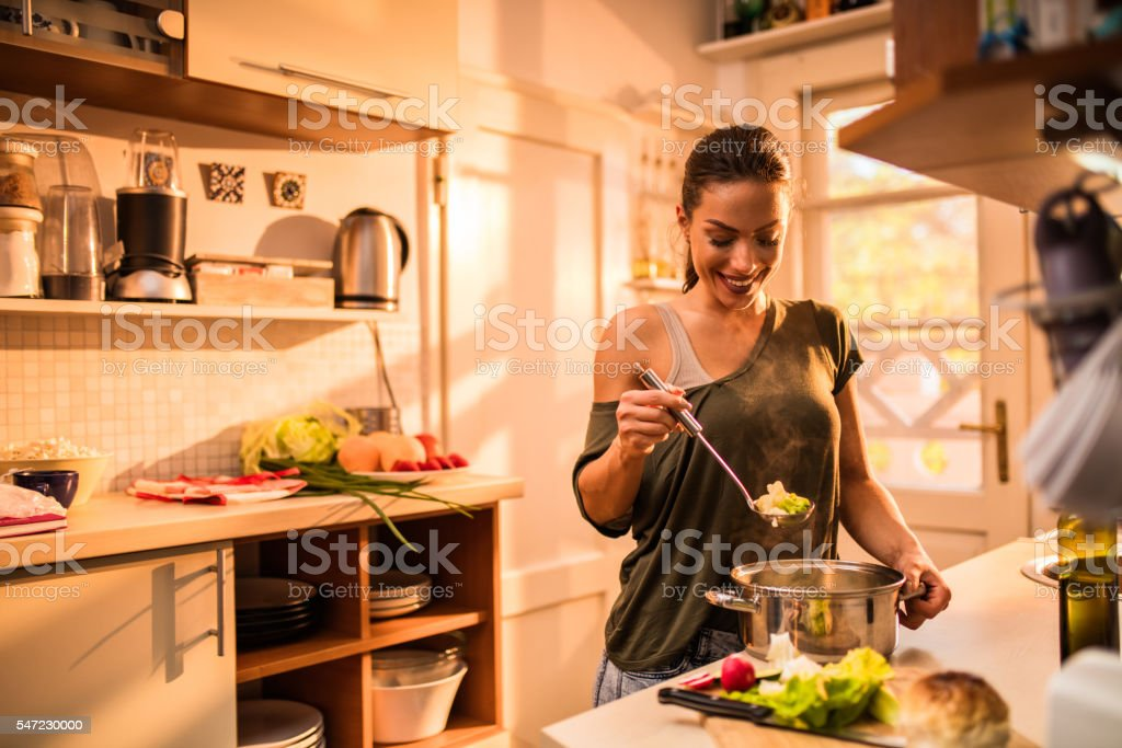 Young smiling woman cooking vegetables in the kitchen. stock photo