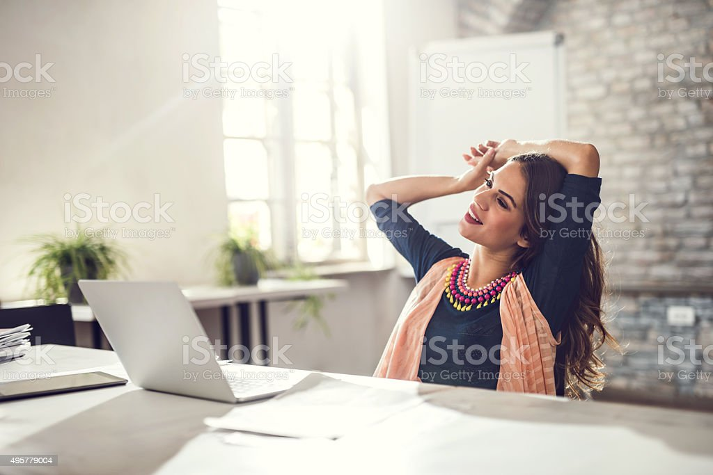 Young smiling woman day dreaming in the office. stock photo