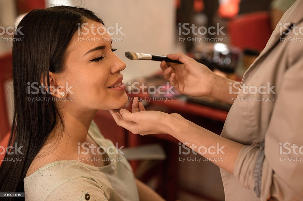 Young smiling woman during make-up treatment. stock photo