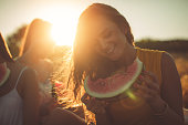 Young smiling woman eating watermelon outdoors